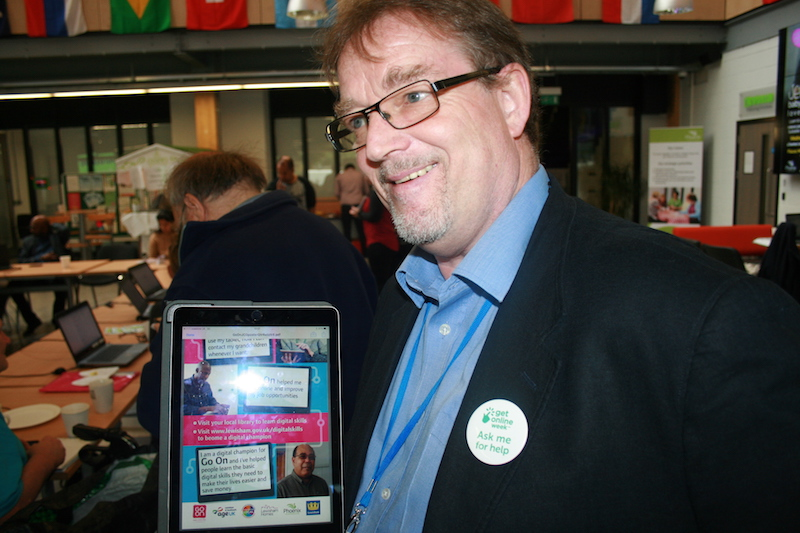 A photo showing digital champion and Go ON Lewisham coordinator, Liam Barnes, showing a promotional flyer