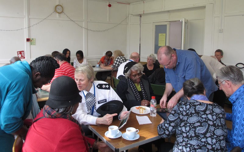 A photo showing the police borough commander helping at a techy tea party for senior residents